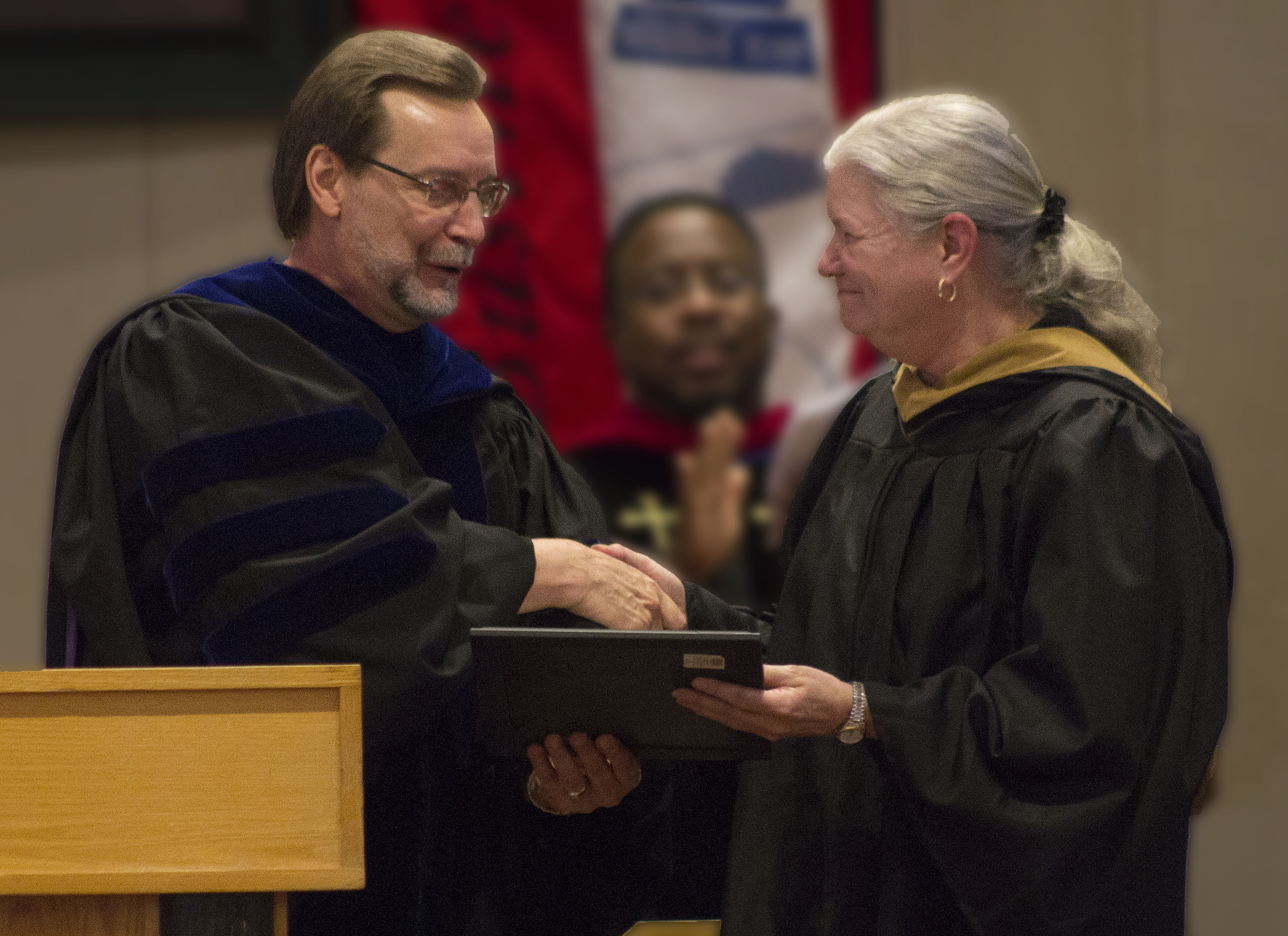 Bacone College's Executive Vice President and Dean of Faculty Dr. Robert K. Brown, left, presents Associate Professor Linda Strange with the Teacher of the Year award at Bacone's recent awards ceremony.
