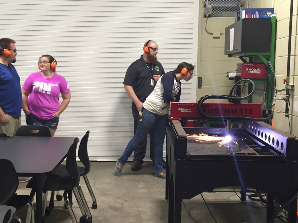 Students observe a fabrication machine in action.