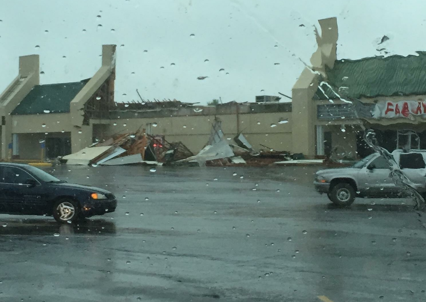 The roof on a store at Curts Center lays in the parking lot