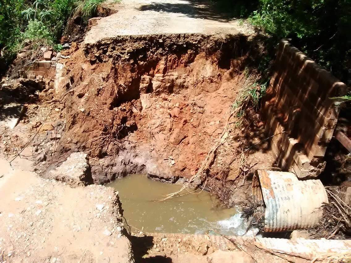 A washed out road reveals a damaged drainage pipe as well.
