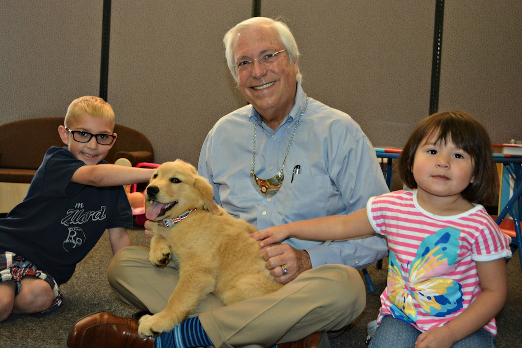 Seven-year-old Tripp Rozell, Cherokee Nation Principal Chief Bill John Baker and two-year-old Sydney McGavock welcome ICW's new therapy dog Unali to the program.