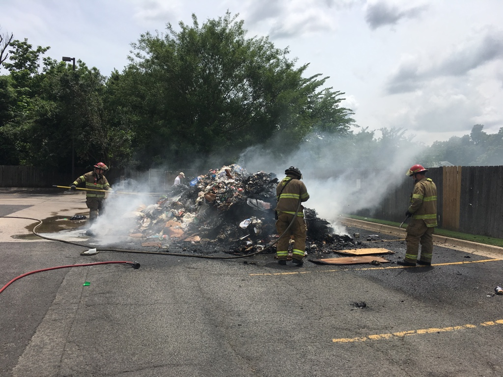 Trash smolders as firefighters work to extinguish it.