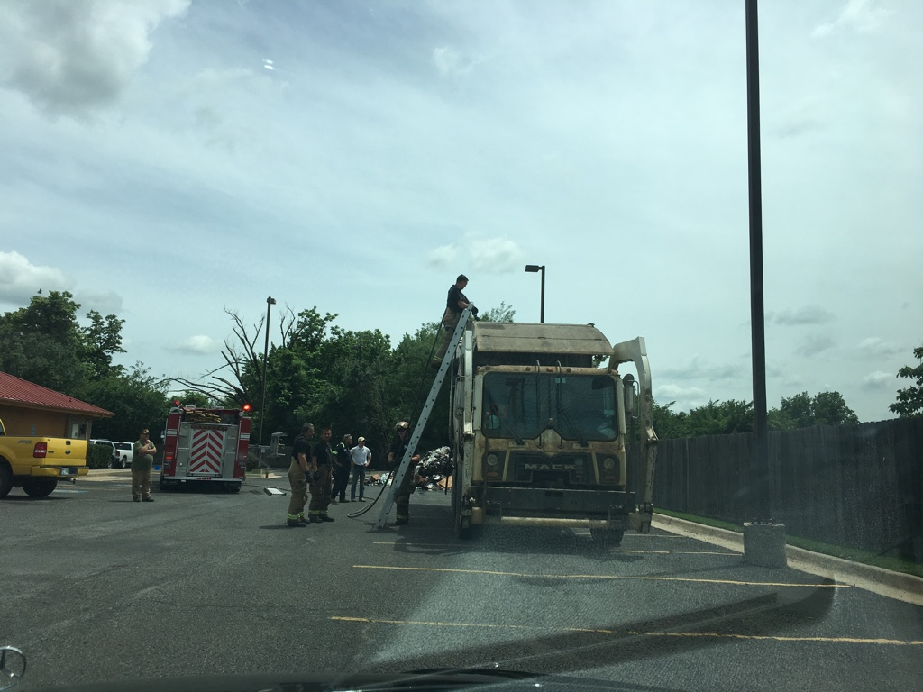 Firefighters work on the trash truck.