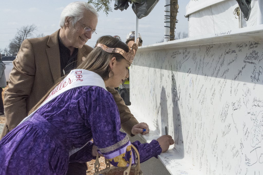 Miss Cherokee Madison Whitekiller and Principal Chief Bill John Baker sign their names to the final steel beam placed on the W.W. Hastings expansion.