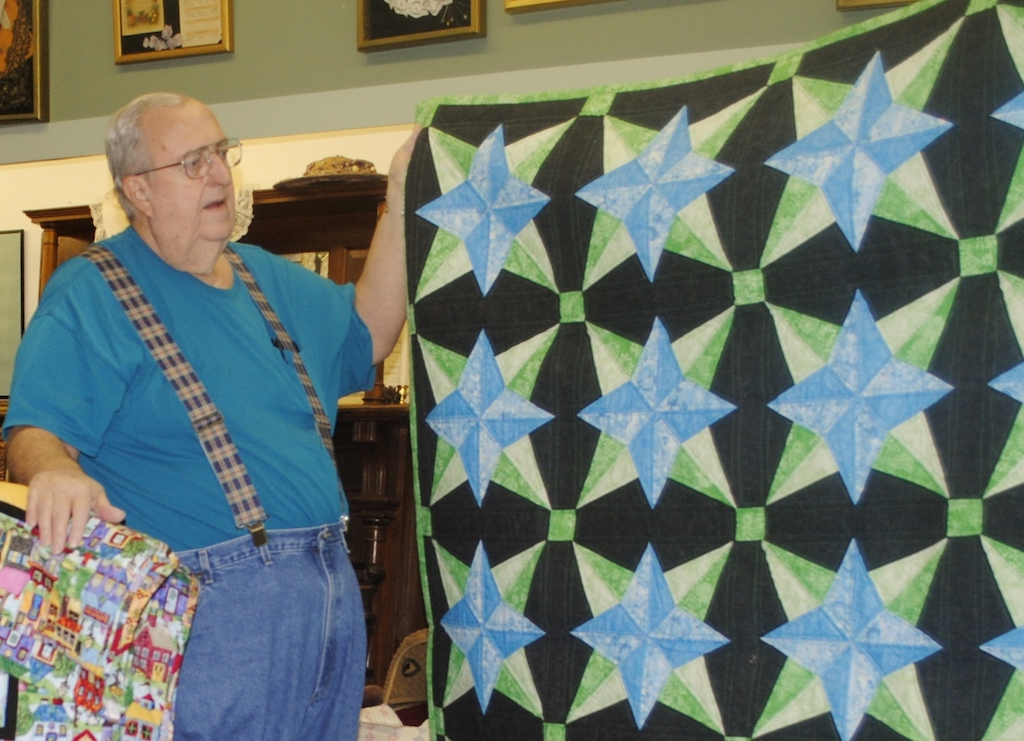 Phil Mackey of Wagoner shows one of the 40 quilts he has made since he took up the hobby a few years ago. He and his wife Janelle have taken the couch out of their travel trailer to make room for the sewing machines each of them uses in their crafting.