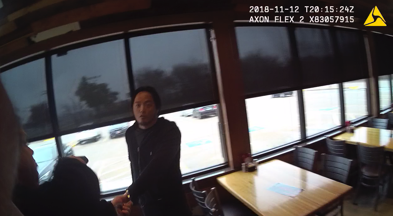 Suspect Andrew Kana looks at Officer Jarad Jones as Sgt. Ron Yates tells him to show his hand. At the time, Kana was allegedly holding a pistol in the hand the officers couldn't see. Click the image to watch the video.