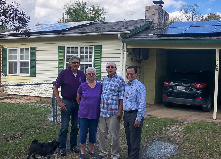 Cherokee Nation Tribal Councilor Harley Buzzard, Linda and Johnny Gifford, and Secretary of State Chuck Hoskin Jr. at the Giffords' home where solar panels have been installed.