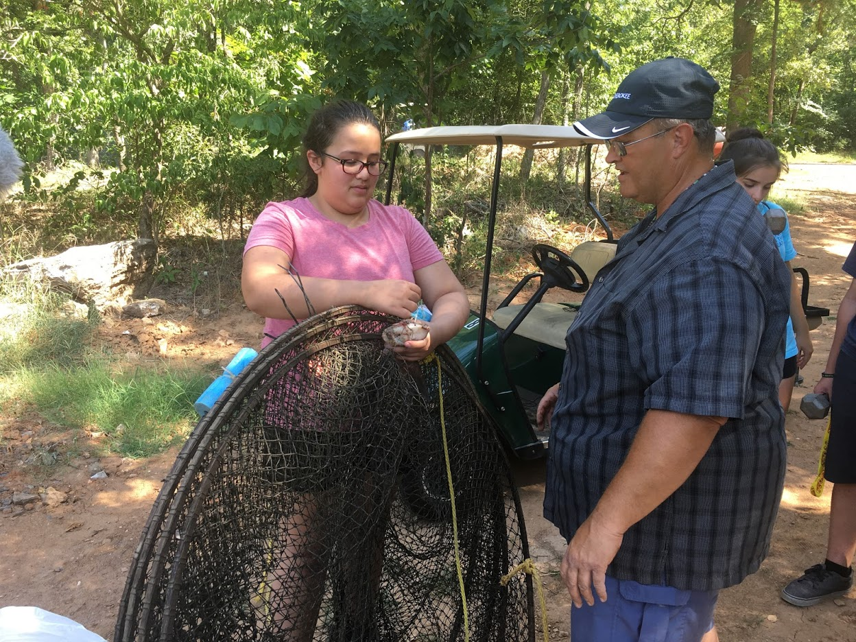 Camp Cherokee participant Ella Mounce baits the hook of a turtle trap as fish and wildlife camp instructor Dr. Paul Shipman observes during the 2018 residential camp.