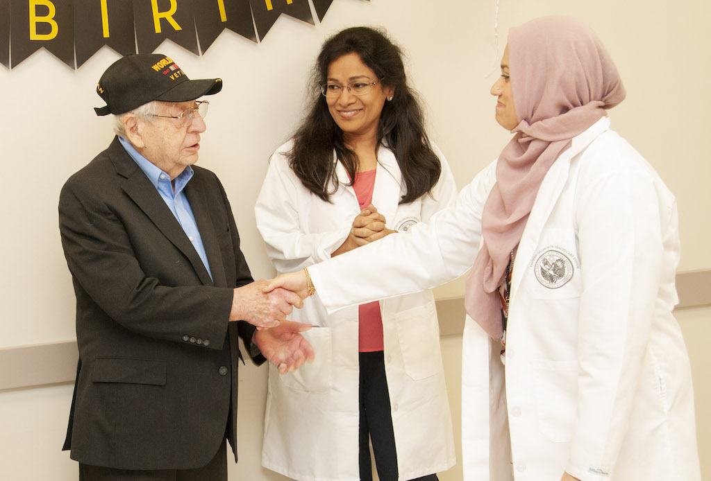 Dr. Saima Salim (right), Chief of Primary Care, wishes World War II Veteran Harry Friedberg a happy birthday during a surprise party at the Ernest Childers VA Outpatient Clinic.
