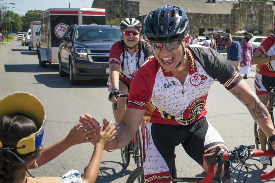 Remember the Removal Bike Ride cyclist Manuel Hernandez, of the Big Y community in North Carolina, is greeted with high-fives after arriving in Tahlequah on Thursday.