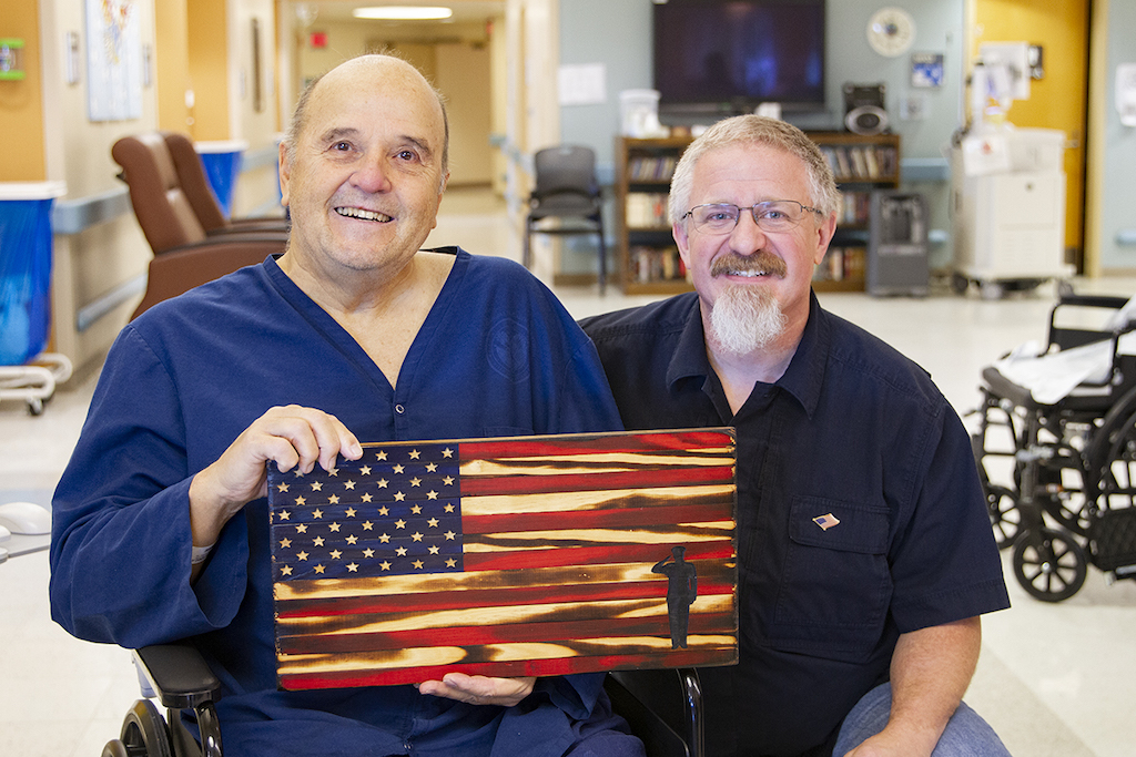 Daryl Thomas, owner of Diamond T Woodcrafts (right), presents Marine Veteran Tom Jones with a hand crafted wooden flag to thank him for his service.