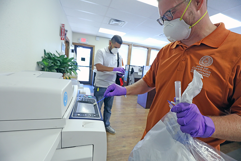 Cherokee Nation Environmental Specialists Nick Clark and Logan Girty swab a high-touch surface with an environmental testing swab that will be tested for traces of COVID-19 to ensure employees are safe and that the tribe's sanitation tactics are working in the fight against COVID-19.