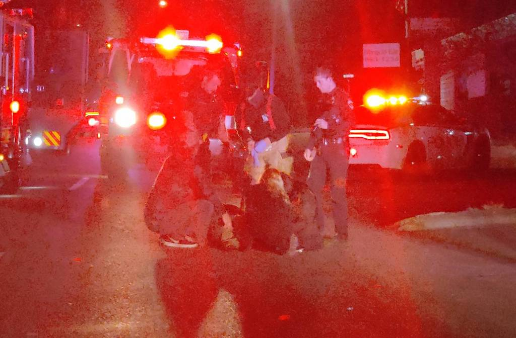 Emergency workers tend to the victim of a hit by a car.